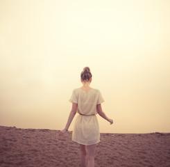 beautiful girl on the beach in the morning fog