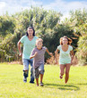 Family of three running on grass