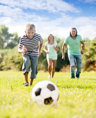 boy with parents playing with soccer ball