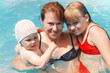 Mother and two her daughters smile in bright sea water