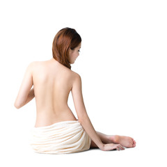 Asian woman wearing towel sitting on the floor back view