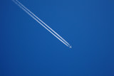 A long trail of jet plane on blue sky