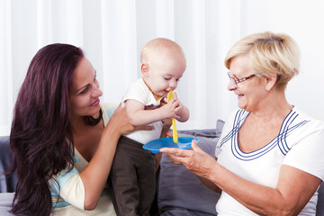 A grandmother feeding the baby with the mother.