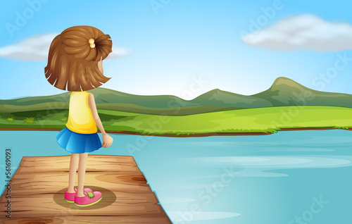 A little girl standing at the wooden port