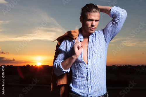 casual man with hand through hairwith sunset behind