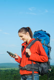 Hiker young woman holding in her hand GPS