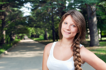 Beautiful teenage girl with long braid in the park