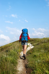 Hiking young woman with backpack and trekking poles