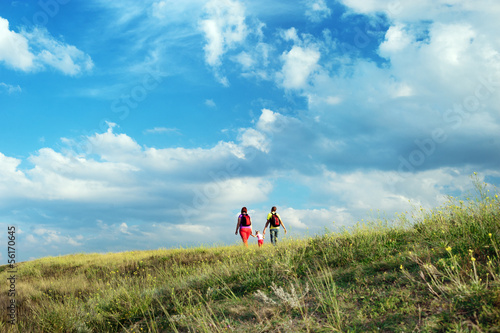 Happy family walking on a meadow