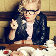 Portrait of hipster blonde girl in trendy glasses eating cake
