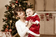 mother and baby in front of Christmas tree at home