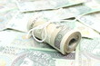 Closeup of roll of tied banknotes on money background