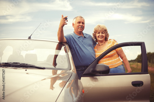 Two elderly people nesr car with keys