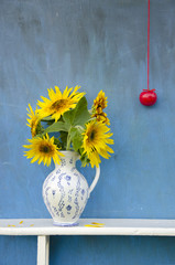 sunflowers beautiful bouquet in  pitcher with red apple