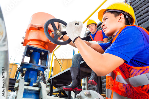 Technicians working on valve in factory or utility