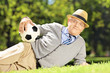 Senior man with hat lying on a grass holding a ball in a park