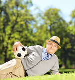 Senior man with hat lying on a grass and holding a soccer ball