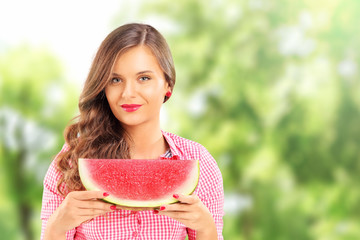 Smiling woman holding a slice of watermelon in a park