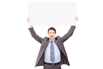 Young smiling businessman holding a blank panel