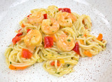 A close view of angel hair pasta with shrimp on a dish