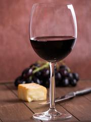 Ein Glas Rotwein mit Käse und Weintrauben
