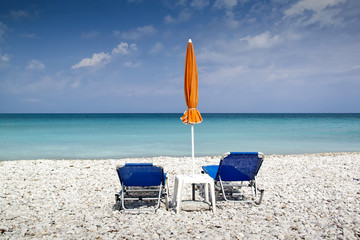 Sun lounger and umbrella on empty beach