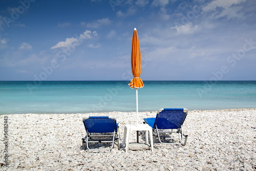Sun lounger and umbrella on empty beach
