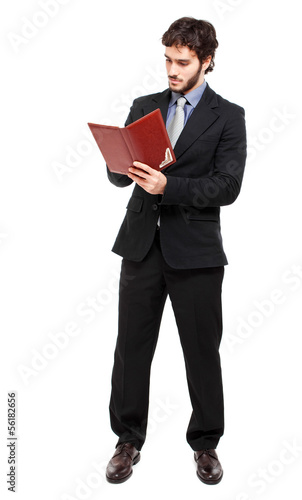 Full length businessman reading his agenda