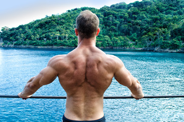 Muscular young man's back. Leaning on metal railing