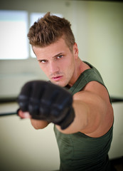 Handsome young man with boxer's gloves