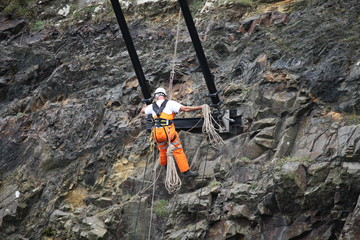 Construction worker climbing rock on cliff face