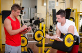 Fotoroleta Personal trainer helping client in gym
