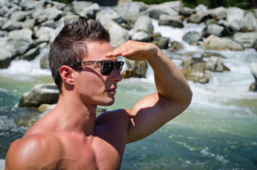 Attractive young muscular man shielding eyes with hand