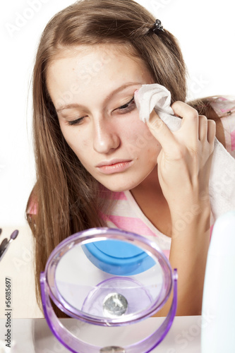 girl wipes mascara and eye make-up using wet wipes