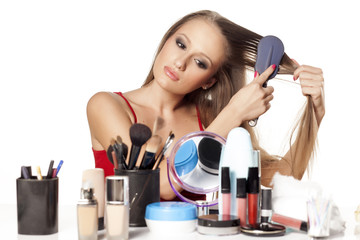 attractive girl combs her hair in front of a table with makeup