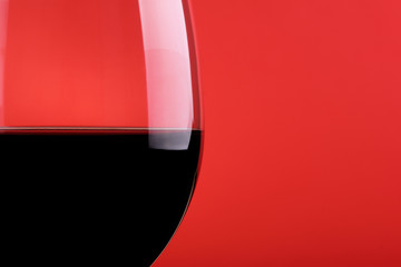 Red Wine glass on red background - closeup