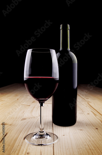 Red Wine bottle and glass on the wooden table - dark background