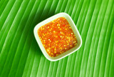 spicy thai sauce on green banana leaf