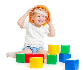 happy kid boy in hard hat playing with colorful building blocks