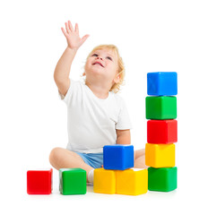 kid playing with colorful building blocks and looking up