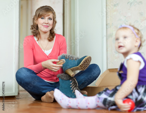 Woman with baby girl cleans shoes