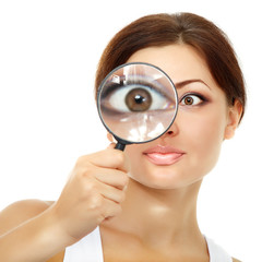 Smiling attractive woman looking through a magnifying glass over