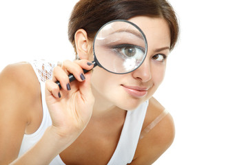 Attractive woman looking through a magnifying glass