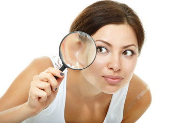 Smiling attractive woman looking through a magnifying glass