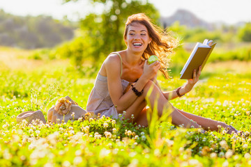 girl with book sitting on grass