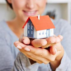 Hands holding a little house