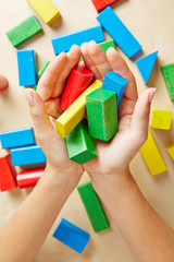 Two hands holding building blocks