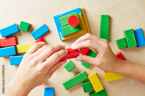 Hands building tower with building blocks