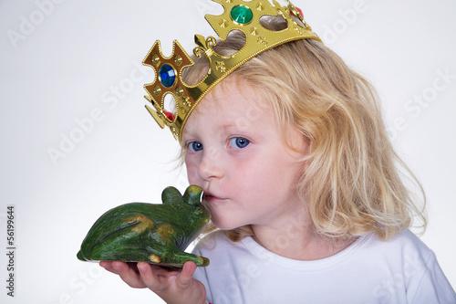 Junges Mädchen mit Krone küsst Frosch