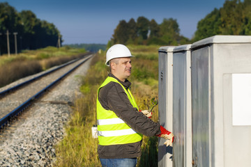 Railroad employee with  near the electrical enclosure